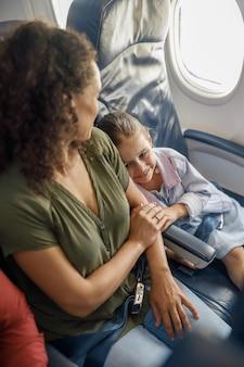 Hoge hoekmening van klein meisje zittend in het vliegtuig, leunend op haar moeder terwijl ze samen reizen. familie, vakantieconcept