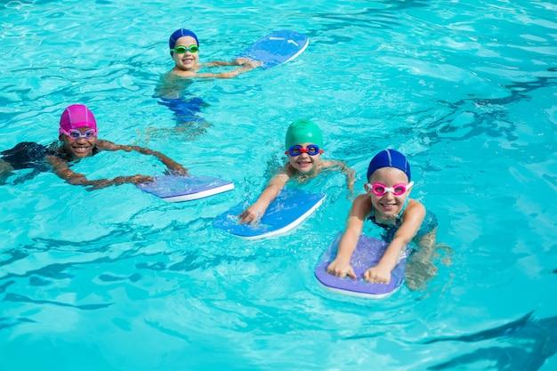 Hoge hoekmening van kleine zwemmers met kickboards die in zwembad genieten