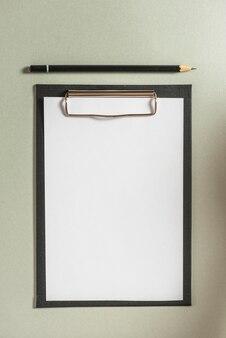Hoge hoekmening van klembord met leeg witboek en potlood