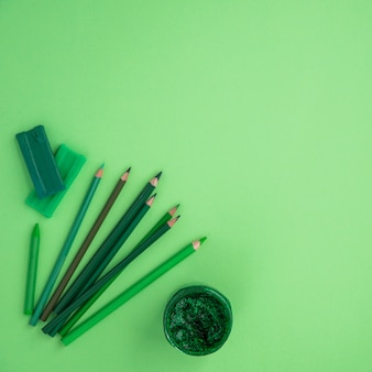 Hoge hoekmening van kleurenpotloden; krijt; klei en glitter kleur over groene achtergrond