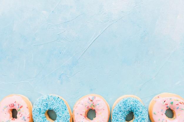 Hoge hoekmening van kleurrijke donuts aan de onderkant van de blauwe achtergrond