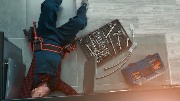 Hoge hoekmening van klusjesman in uniform liggend op de vloer in de keuken en het gebruik van moersleutel tijdens het repareren van de waterleiding in de keuken. gereedschapskist op de vloer. horizontaal schot