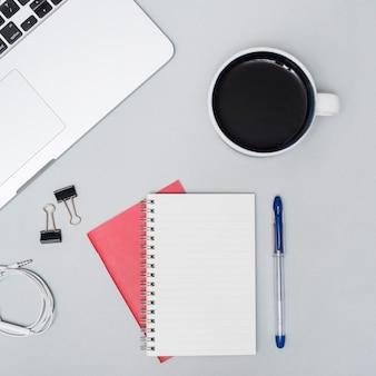 Hoge hoekmening van koffiekop; laptop; spiraal notitieboekje; oortelefoon; pen; tegen grijze achtergrond