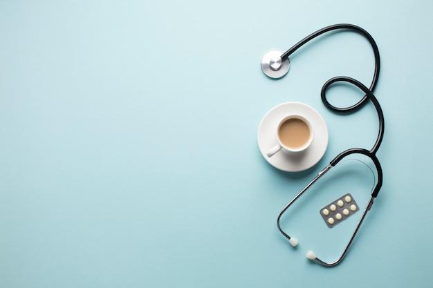 Hoge hoekmening van koffiekopje; stethoscoop en medicijnen in blisterverpakking op blauwe achtergrond