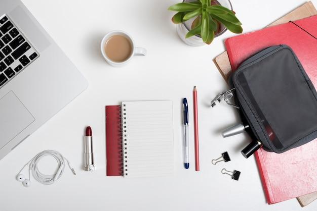 Hoge hoekmening van laptop; make-up tasje; oortelefoon en koffiekop en dossiers over wit bureau