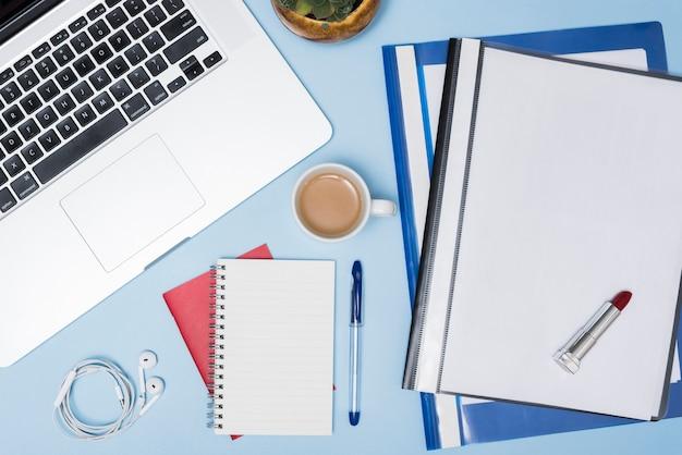 Hoge hoekmening van laptop; mappen; koffiekop; oortelefoon; spiraal blocnote en pen tegen blauwe achtergrond