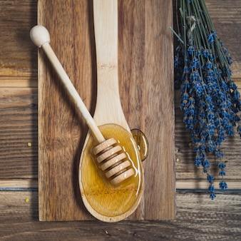 Hoge hoekmening van lavendel en houten dipper op lepel met honing
