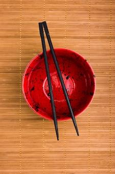 Hoge hoekmening van lege kom met zwarte chopstick over placemat