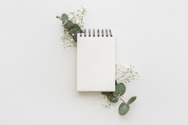 Hoge hoekmening van lege spiraal blocnote met bladeren en baby adem bloemen op wit oppervlak