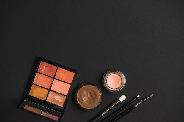 Hoge hoekmening van lippenstift; crème foundation en make-up borstels op zwarte achtergrond