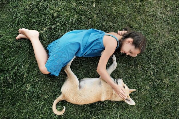 Hoge hoekmening van meisje liggend op het gras met haar hond en spelen op frisse lucht