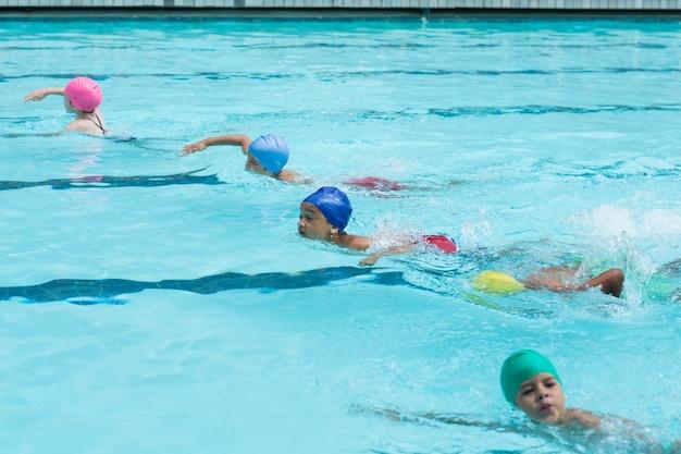 Hoge hoekmening van meisjes en jongens die in zwembad zwemmen
