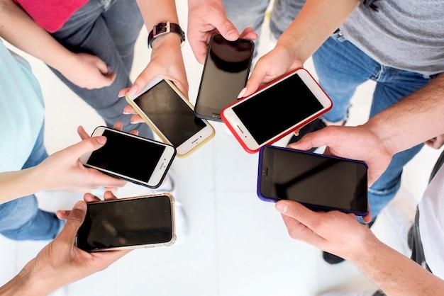 Hoge hoekmening van mensen die mobiele telefoons gebruiken