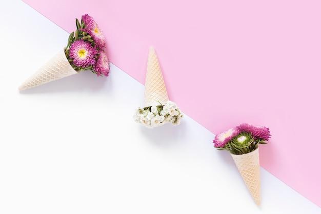 Hoge hoekmening van mooie bloemen in de kegel van het wafelroomijs op dubbele achtergrond
