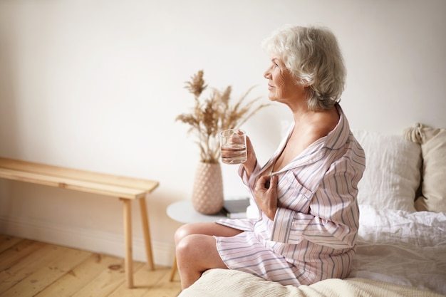 Hoge hoekmening van mooie sensuele kaukasische zestig-jarige volwassen vrouw in zijden pyjama, haar schouder ontbloot zittend op de rand van bed, drinkwater na het ontwaken, met een gelukkige blik