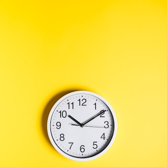 Hoge hoekmening van muurklok op gele achtergrond