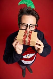 Hoge hoekmening van nerd man met klein kerstcadeautje