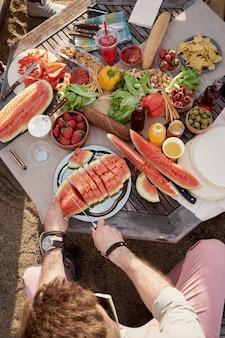 Hoge hoekmening van onherkenbaar man rijpe watermeloen buiten snijden zittend aan tafel met smakelijk vers fruit en groenten
