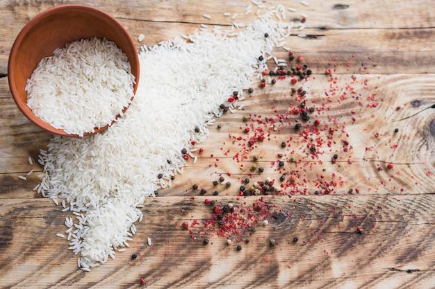Hoge hoekmening van organische rijst in kom en zwarte peperskruid over houten behang