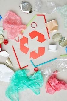 Hoge hoekmening van pakkettenflessen en blikjes rond het rode recyclingsymbool