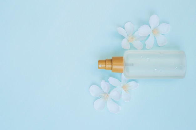 Hoge hoekmening van parfumfles met witte bloemen op blauwe achtergrond