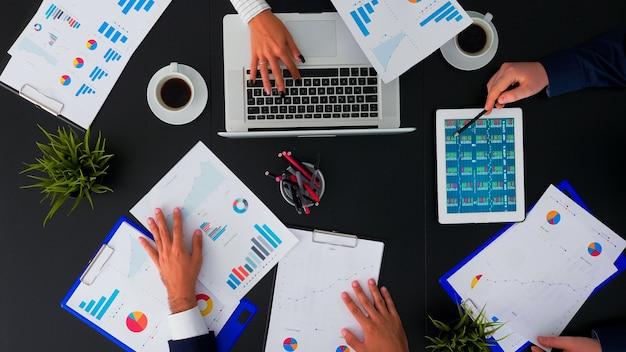 Hoge hoekmening van professionele zakenmensen die in vergaderruimte bijeenkomen met bedrijfsmanager die financiële strategie plant met behulp van moderne technologie in bedrijfsgebouw