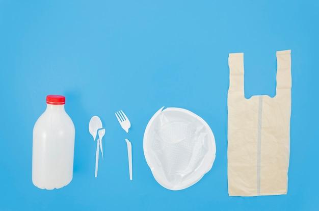 Hoge hoekmening van rij van plastic afval over blauwe achtergrond