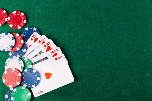 Hoge hoekmening van royal flush clubs en chips op groene pokertafel