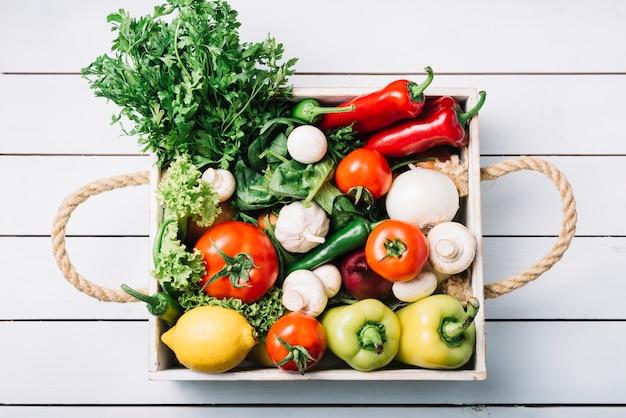 Hoge hoekmening van ruwe organische groenten in container op houten achtergrond