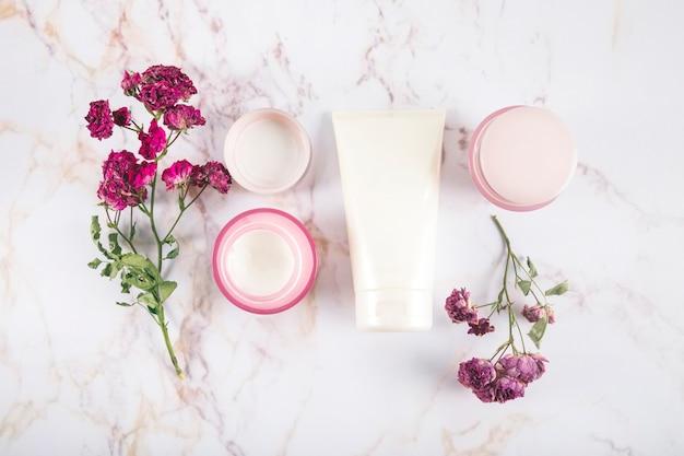 Hoge hoekmening van schoonheid crèmes en bloemen op marmer