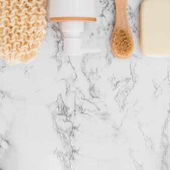 Hoge hoekmening van scrub handschoen; cosmetische fles; zeep en borstel op marmeren oppervlak
