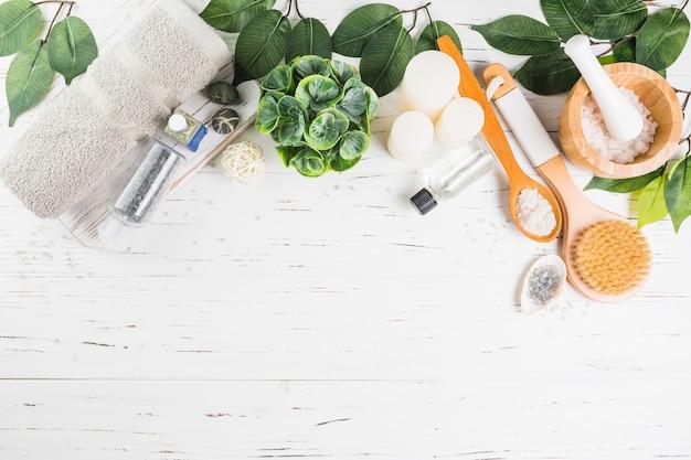 Hoge hoekmening van spa-producten met groene bladeren op houten plank