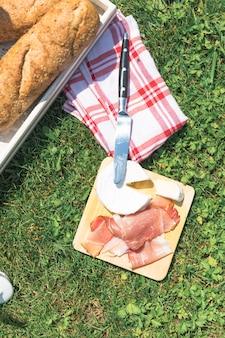 Hoge hoekmening van spek; kaas en gebakken brood op gras