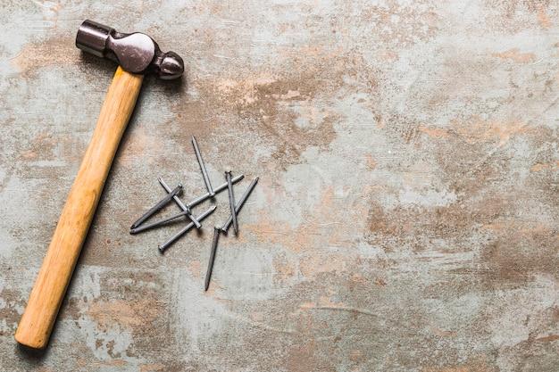 Hoge hoekmening van spijkers en hamer op roestige houten achtergrond