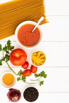 Hoge hoekmening van stuiver en spaghettideegwaren met ingrediënten op witte lijst