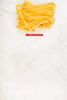 Hoge hoekmening van tagliatelle pasta op marmer