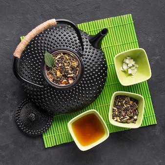 Hoge hoekmening van theepot met gedroogd kruid en witte jasmijnbloem op groene placemat