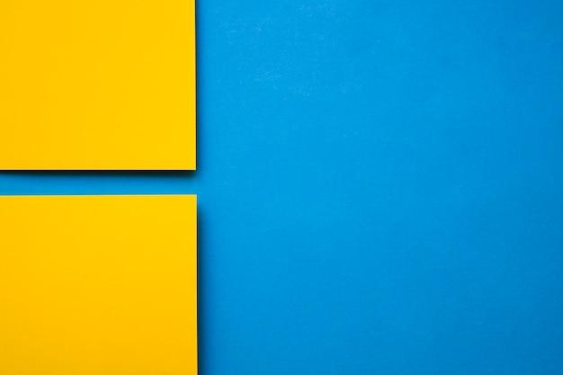 Hoge hoekmening van twee gele kartondocumenten op blauwe achtergrond
