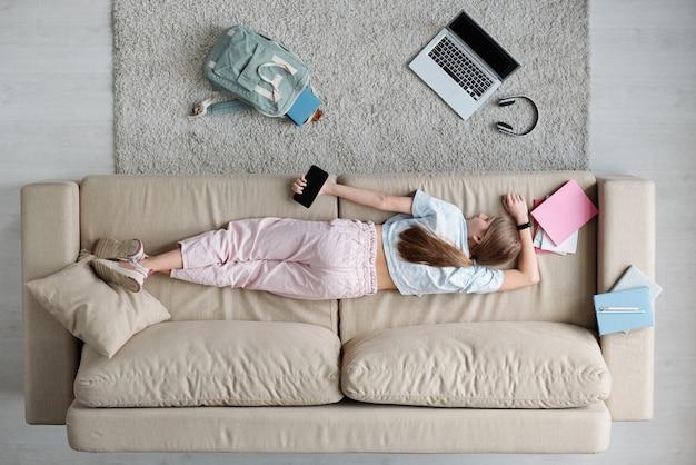 Hoge hoekmening van vermoeide tienermeisje slapen met telefoon in hand op de bank in de woonkamer, ze rust na school