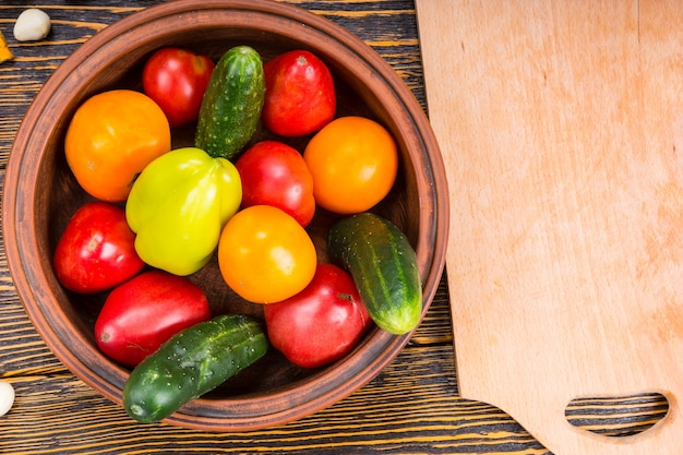 Hoge hoekmening van vers geplukte groenten in kom naast houten snijplank op rustieke houten tafel met houtnerf