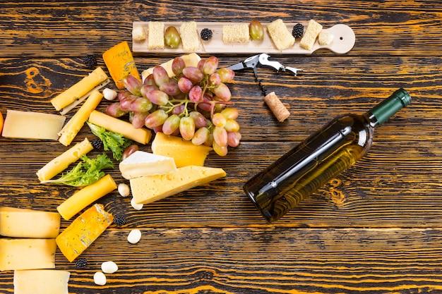 Hoge hoekmening van verscheidenheid aan gastronomische kazen verspreid op rustieke houten tafel met druiven en fles witte wijn