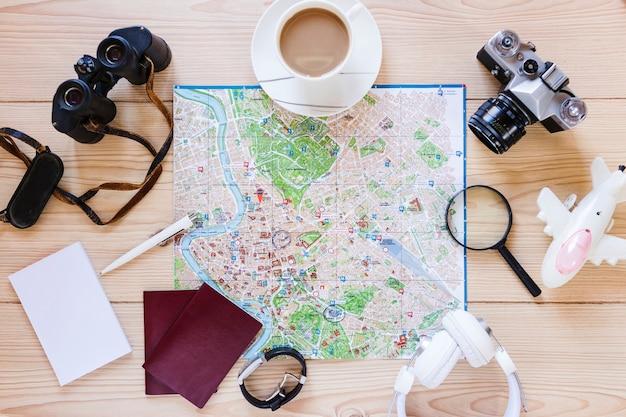 Hoge hoekmening van verschillende reizigerstoebehoren en kop thee op houten oppervlakte