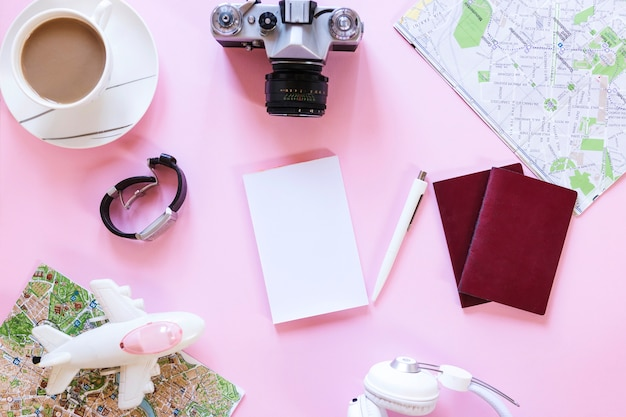 Hoge hoekmening van verschillende reizigerstoebehoren met theekop op roze achtergrond