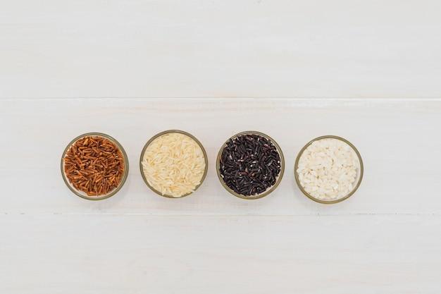 Hoge hoekmening van verschillende rijst in kommen gerangschikt in rij over witte tafel