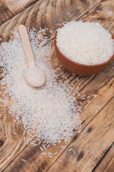 Hoge hoekmening van verse rauwe rijst in kom met kleine lepel over gestructureerde houten achtergrond