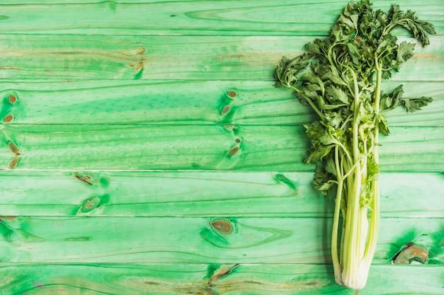 Hoge hoekmening van verse selderij op groene houten achtergrond
