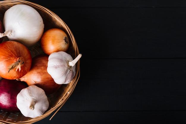 Hoge hoekmening van verse uien en knoflookbollen in mand op zwarte oppervlakte