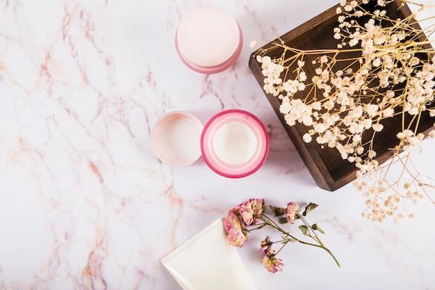 Hoge hoekmening van voedende crème en bloemen op marmer