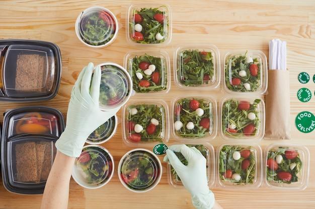 Hoge hoekmening van vrouw in beschermende handschoenen werken aan houten tafel stickers zetten dozen met voedsel voor levering