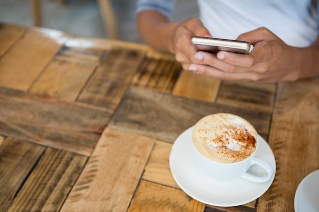 Hoge hoekmening van vrouw met behulp van mobiele telefoon met koffiekopje op tafel in café